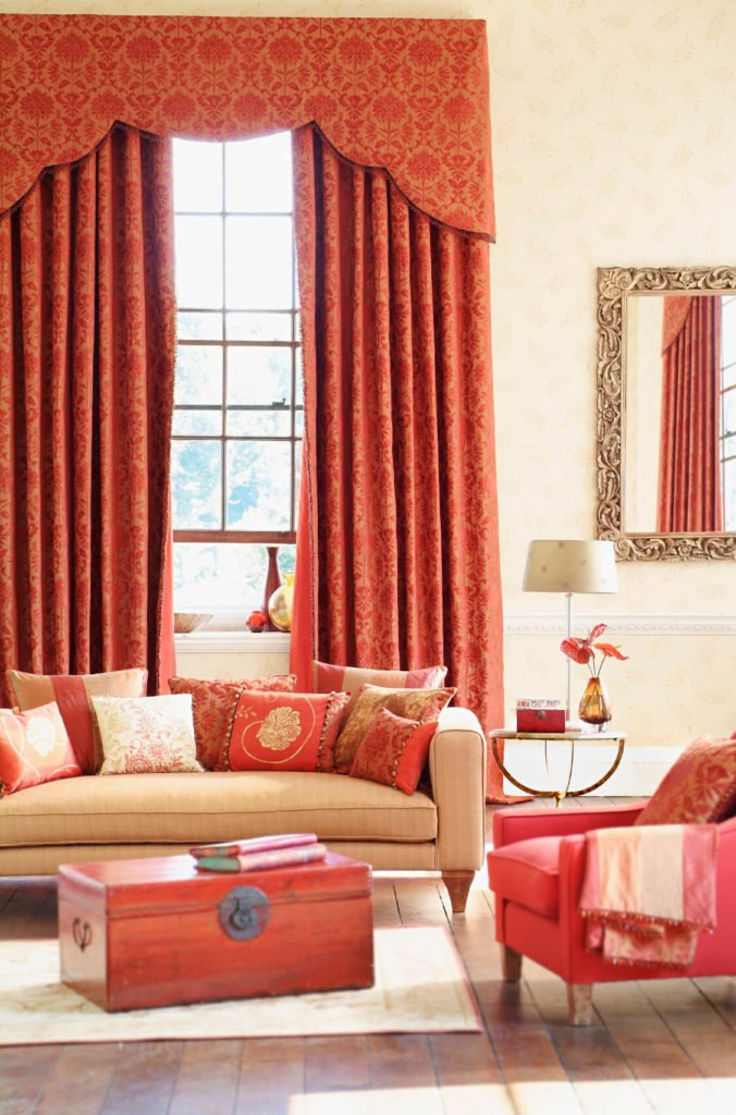 Red damask curtains complement salmon pink in in the furniture. A gilded mirror adds to the luxury of the room.