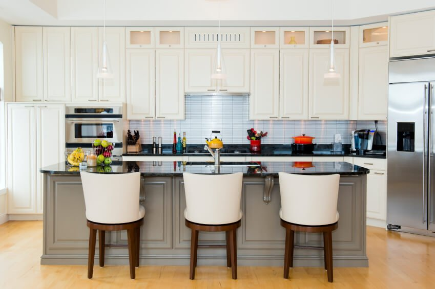The grey of this kitchen island contrasts the bright white of the cupboards while the backsplash adds a bit of color to the room. The light wood floor fills the space with a natural warmth.