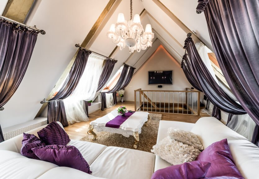 In an attic living room, curtains are draped between and upper and lower curtain rod, creating a tent-like feeling.