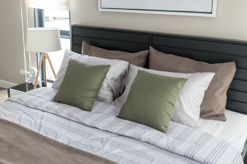 Carefully arranged pillows grace the striped linens of this symmetrical arrangement. The quietly masculine space commands attention without being overwhelming, while a simple headboard oversees the bed offering dark contrast to the neutrals of the room.