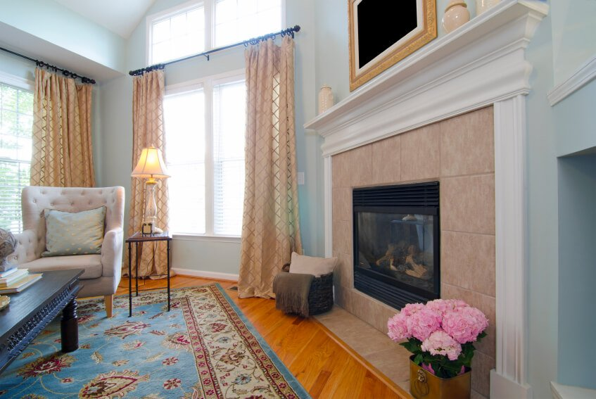 Sheer curtains with a subtle pattern are hung between two sets of large windows in this great room.