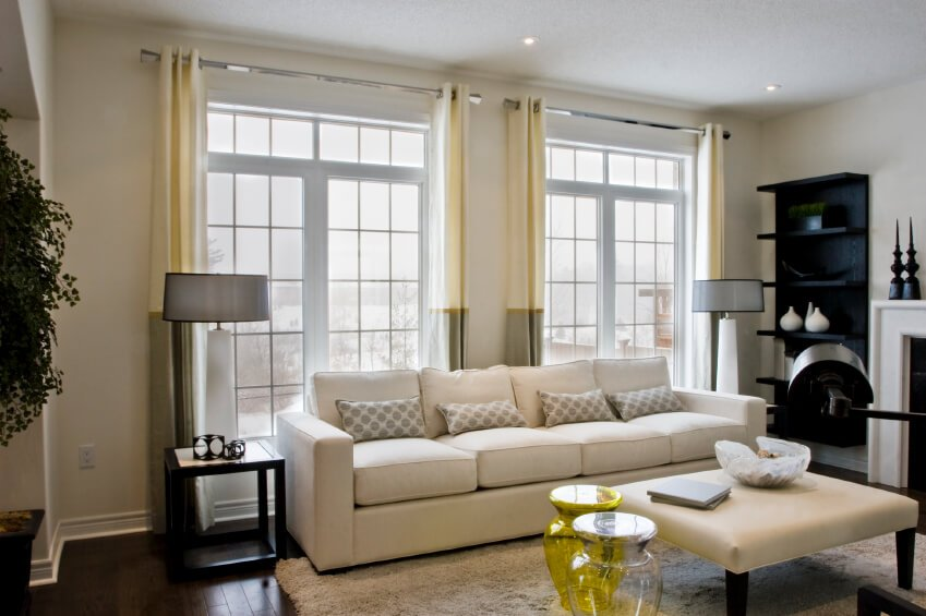 For large windows that are separated by a section of wall, try using two separate sets of curtains, rather than one single one.