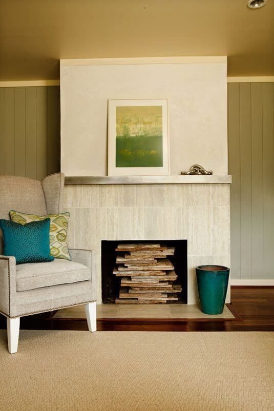 A close up of the fireplace, showcasing the stacked wood that fills the open, unused hearth.
