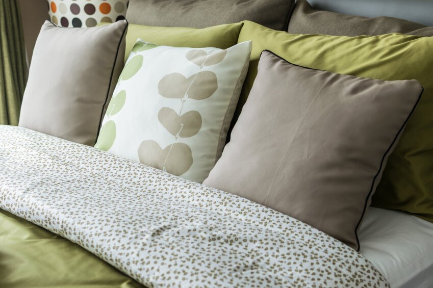 Shades of gray and chartreuse work playfully with each other, creating a vibrant yet understated space. A single patterned throw pillow is flanked by simple gray accent pillows in this symmetrical layout.