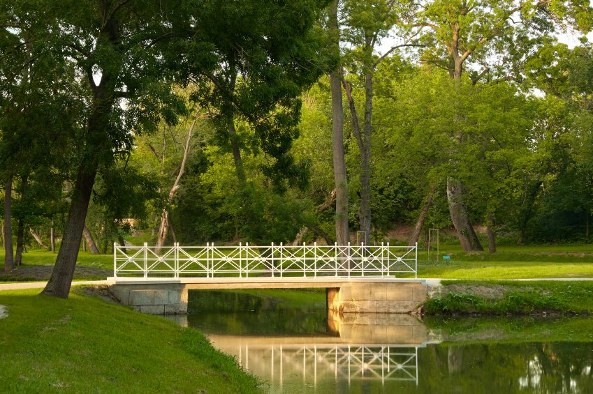 A slim, flat, white bridge expands over a simple pond and stream through a shady park. A wonderful place for an afternoon or evening walk.