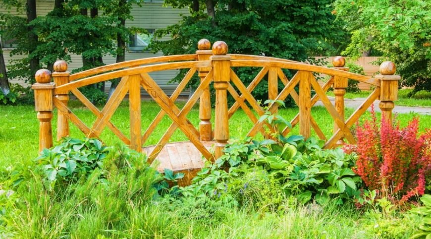 The striking woodgrain of this honey oak garden bridge allows it to stand out in a subtle way against the grass and flowers.