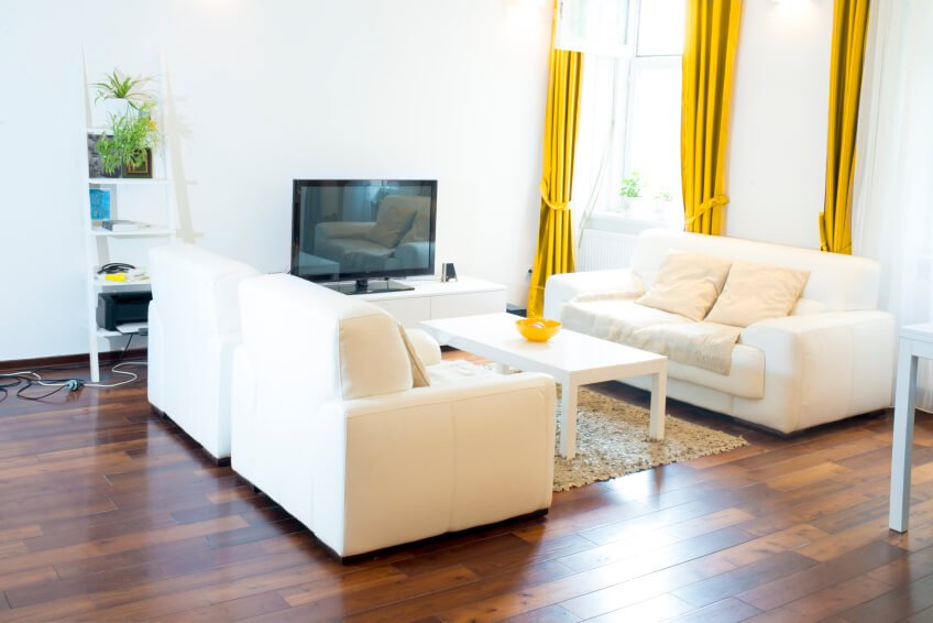 Bold yellow curtain panels make a striking statement in this mostly white and cream living room. The multi-tonal wood floors add warmth as well.