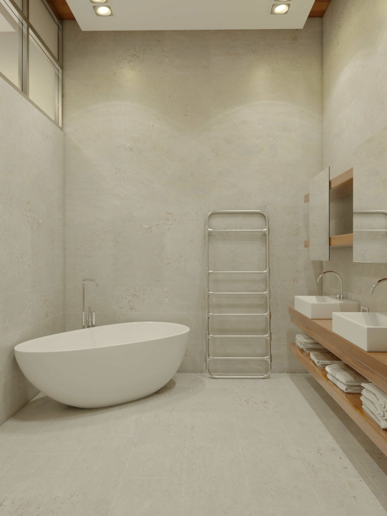 Entering the bathroom, we see an expanse of soft hued concrete from the floor on up. A large curved pedestal tub stands in the corner, across from rich wood dual vanity.