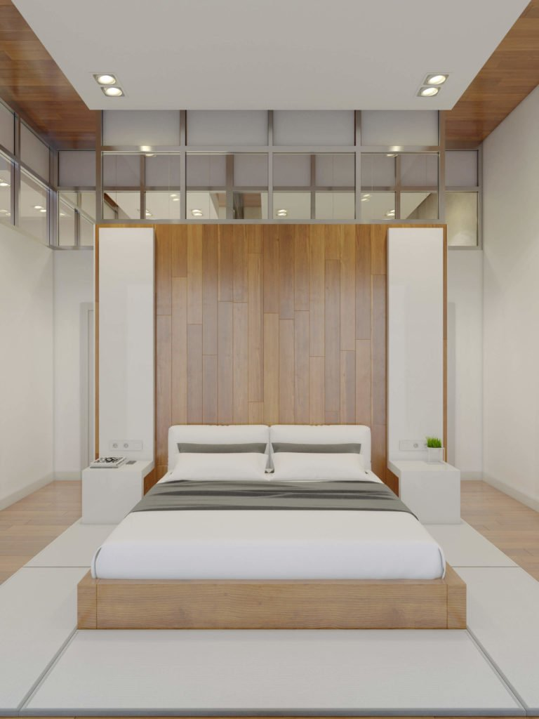 The primary bedroom is an exercise in symmetry, with a large dividing wall doubling as headboard behind the bed. The natural wood frame is mounted on white floor panels.