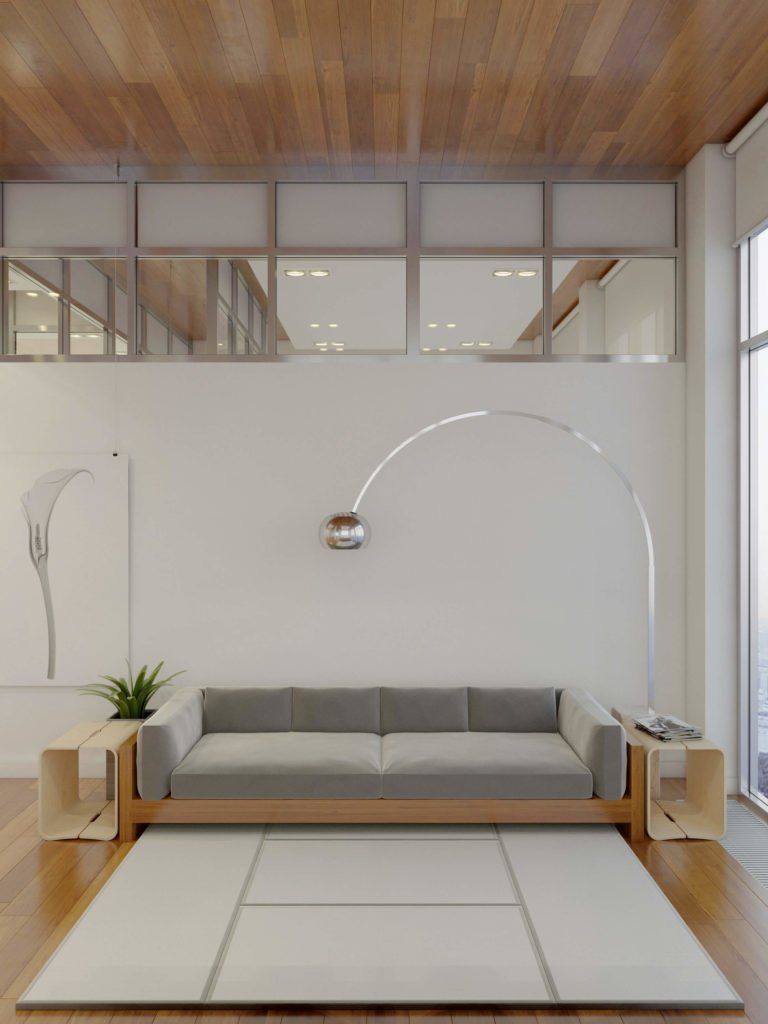 The large wood framed sofa stands flanked by a pair of curved-edge cubic tables mimicking the look of the barstools. A single arched floor lamp provides illumination, beneath the upper level interior windows.
