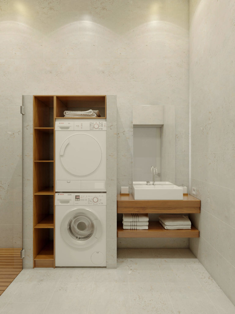Laundry machines are built into a space flanked by cubbies for storage and another floating vanity, with towel storage below the large square vessel sink.