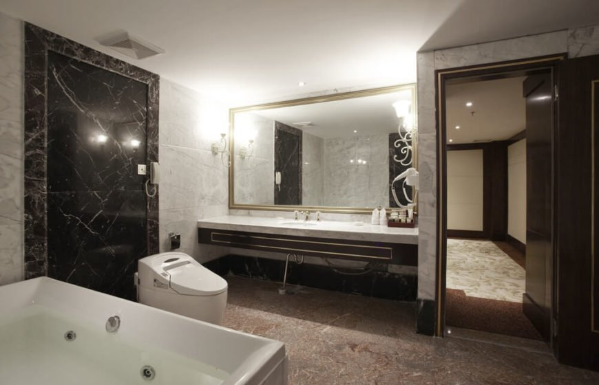 This bathroom features an intense mixture of marble surfaces, from large tiled walls in light grey, to a black detail at left, over darkly rust toned flooring. The minimalist space features a floating vanity below oversized mirror.