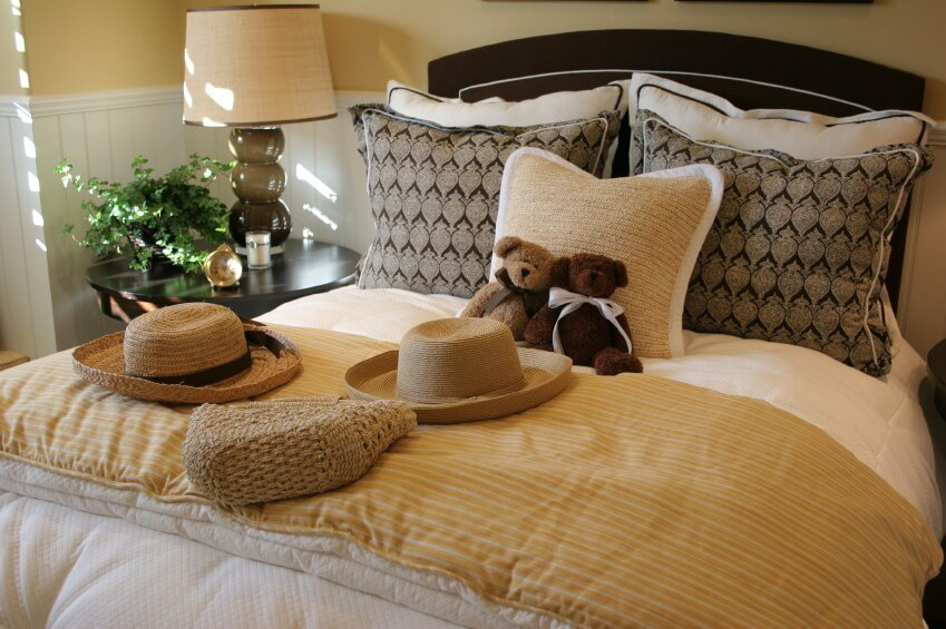 This charming bedroom showcases a variety of colors, patterns and textures. The natural fiber square accent pillow supports two adorable teddy bears, and goes perfectly with a variety of straw decorative accents. The darker rectangular throw pillows behind it offer a spectacular contrast against the lighter bed pillows that they rest against, while the dark headboard provides additional richness and beauty.