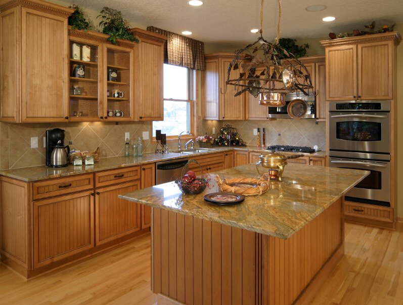 This rustic, woodsy kitchen's floors bring out the pale tan tones of the granite countertops and brighten up the room considerably. Glass door cabinets punctuate the uniformly natural wood look.