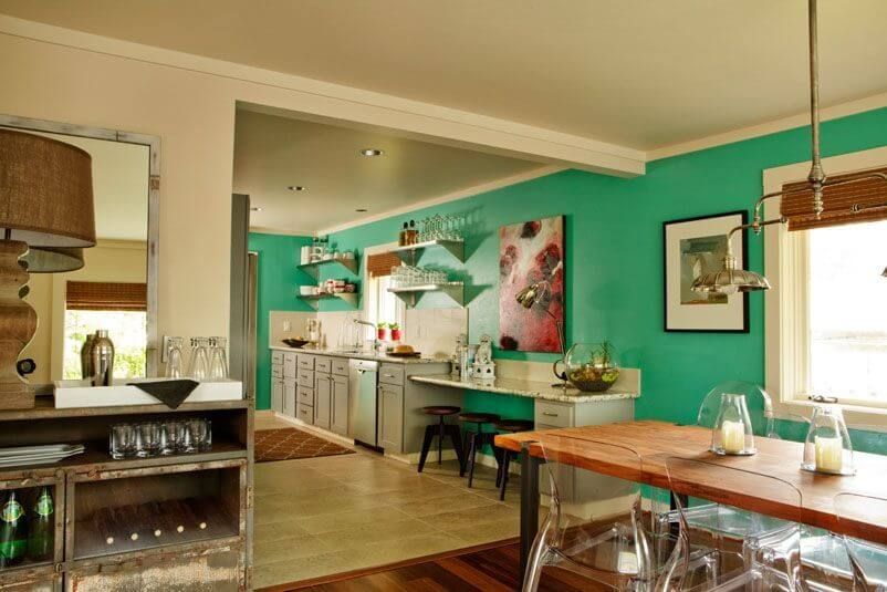 The open-concept dining room and kitchen are in a bold blue-green. The dining set is wood with transparent chairs. The kitchen is in a light beige tile with a white backsplash.