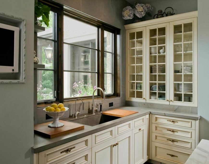 When entering the kitchen, the style of the home shifts in favor of the contemporary. This section of the kitchen features light gray marble countertops with butcher board next to the sink and glass-faced cabinets to the right.