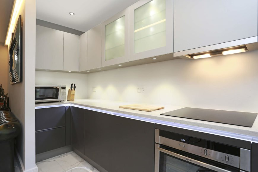 Beneath the countertops is a strip of inner-lighting, highlighting the contrast in this kitchen.