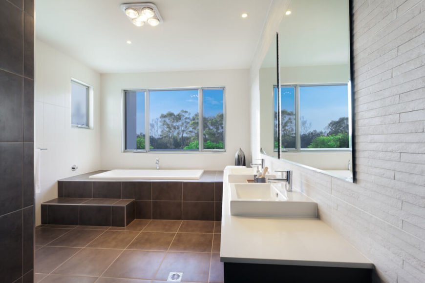 This sleekly modern bathroom features large format dark brown tile flooring, wrapping up and around the enclosure for a soaking tub beneath the window. A large white-topped dual vanity at right features rectangular vessel sinks.