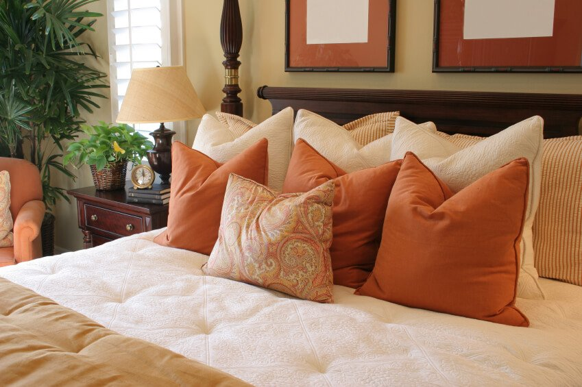 This bright and cheerful space offers lovely pops of color with its vibrant rust colored accent pillows and coordinating chair. A lovely paisley throw pillow marches to the front of the line, while supporting striped and cream accent pillows round out this exceptional grouping.