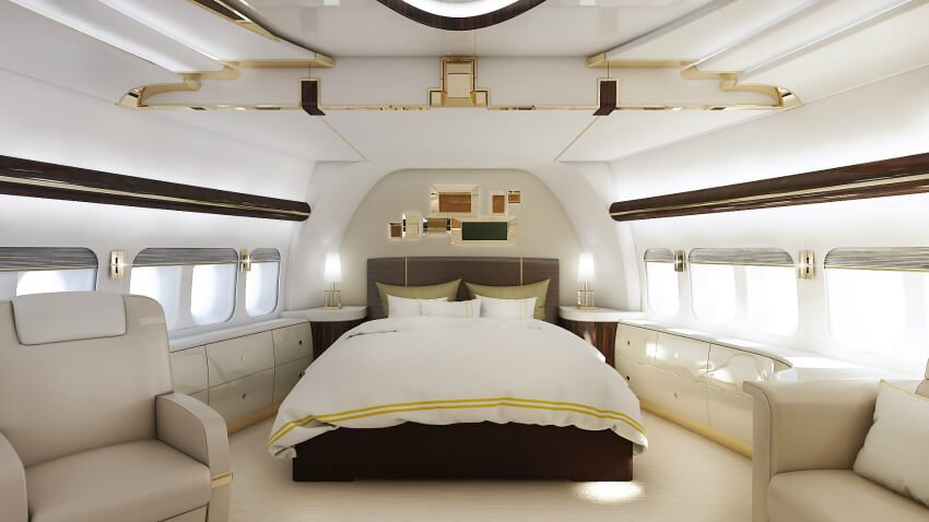 The primary bedroom suite features all the functional space of a proper standard bedroom, with built-in storage and the best views from inside the plane. The bed stands at center, flanked by arrays of sleek cabinetry below the windows, while a pair of club chairs sit in the foreground. Gold accents and rich wood tones abound.