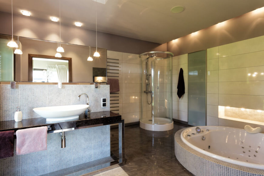Here we have an ultra-modern bathroom featuring a variety of unique elements over a dark marble floor. A large jacuzzi sinks into the floor at right, while a vessel sink vanity at left creates a dividing wall. Circular glass enclosed shower stands in the corner.