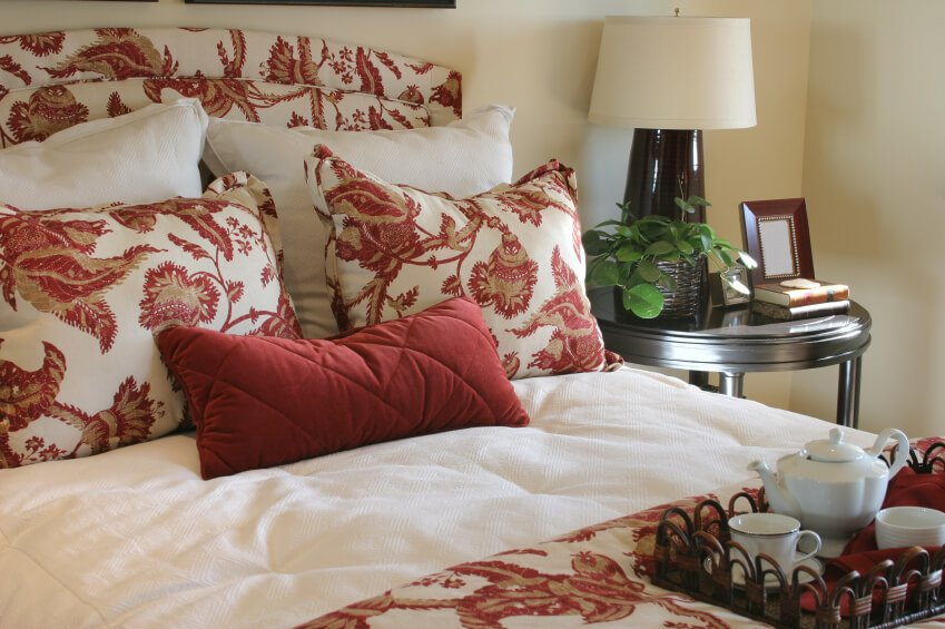 Matching headboard, pillows, and duvet cover are interrupted by blanche pillows and a deep crimson lumbar accent throw pillow.