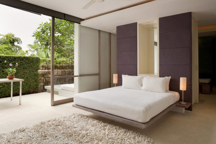 The primary bedroom has a sliding door that leads out into a courtyard with stone walls and hedges. This room faces the interior of the island, rather than the water.