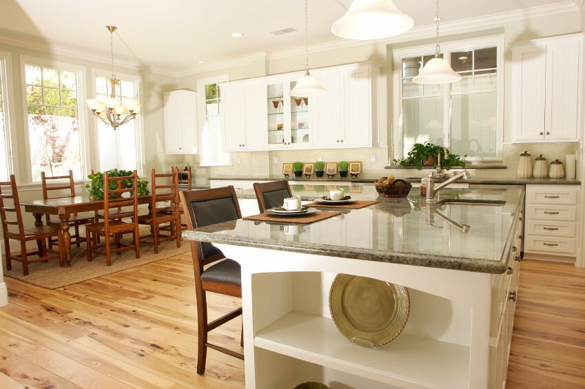 The beautiful knotty texture of this floor only stands out more with the use of white cabinets and cool grey granite counters. Dark wood dining furniture accents the palette perfectly.