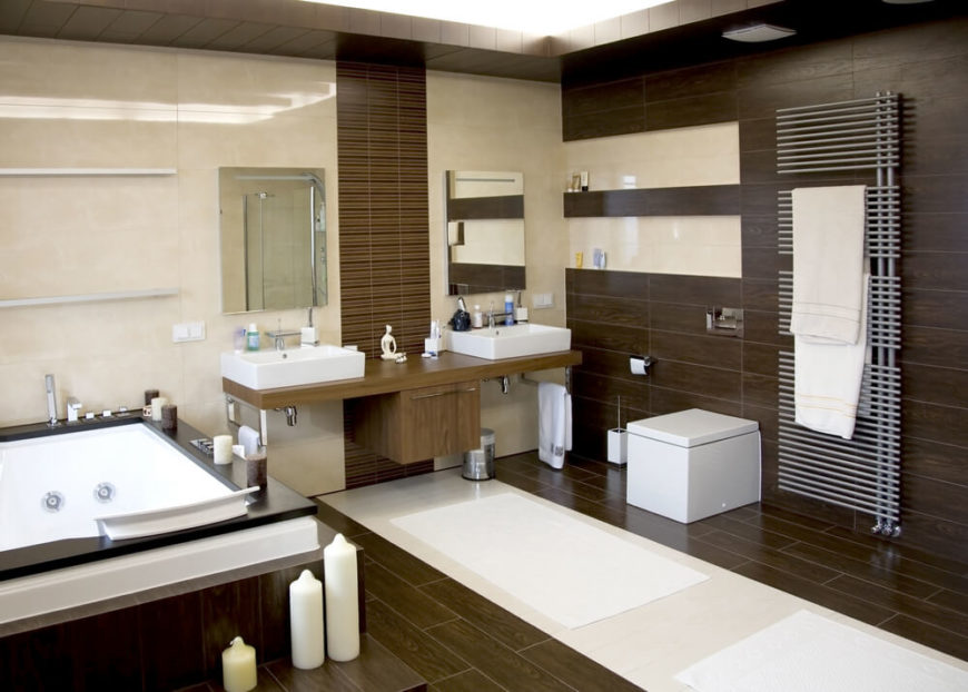 This Zen-like bathroom highlights an attention to texture and balance, with dark toned wood panel flooring and right wall, paired with beige marble wall. The floating dual vanity in wood holds a pair of vessel sinks, while a large soaking tub stands framed in dark wood at left.