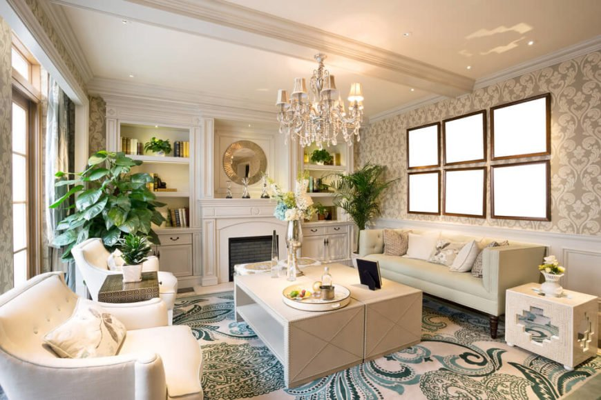 A bold white and blue living room with a beautiful crystal chandelier above the coffee table. The coffee table is actually two separate, narrower tables pushed together. They can be slid apart if needed to serve either side of the room. The room has one small additional end table, which has cut out mirrors on the tile that reflect light back into the room.