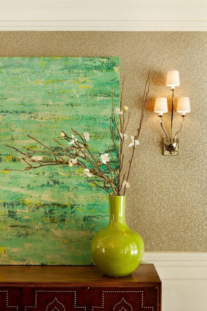 A close up on the buffet in the dining room, focusing on the speckled walls and the accents. The lime-green vase filled with dogwood blossoms picks up the same green in the painting.