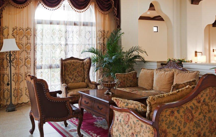 In another traditional French Country living room, the windows are covered by a sheer patterned curtain, which is framed by rich cream colored curtains in the same pattern. The display is topped by a tasseled valance in burgundy.