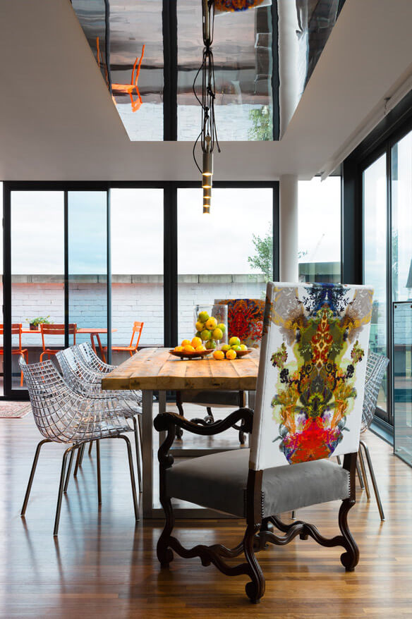 A final daytime look at the dining room from one end shows the expansive windows and a view onto the terrace.