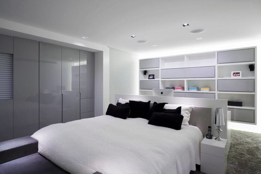 The primary bedroom is also in a pristine white, with a unique layout. Instead of the bed being placed against the wall, the bed is in the center of the room against a slightly taller desk. This arrangement visually separates the two sections of the bedroom: the sleeping area and the work area.