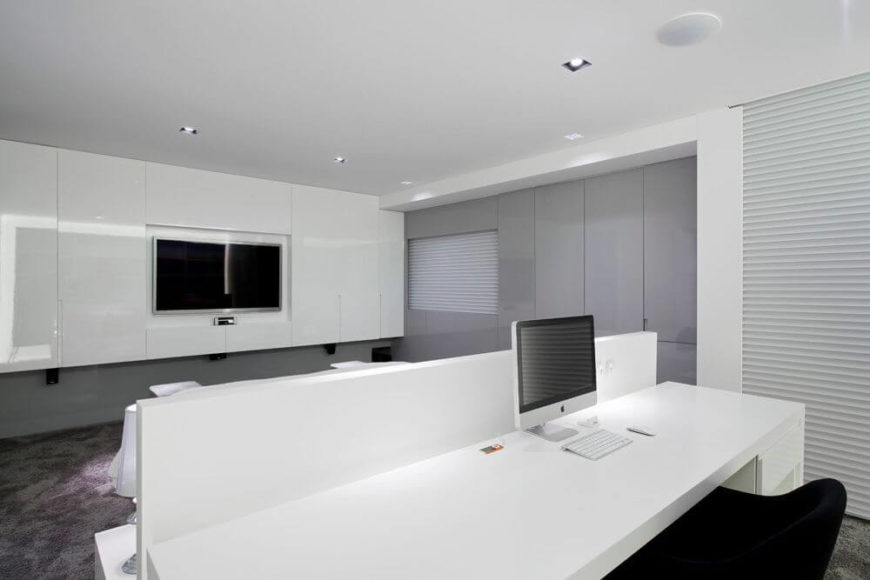 A view over the bed from the desk area. A television inset into the far row of wall cabinets is placed perfectly so that it can be viewed both from the bed, the settee at the foot of the bed, or from the desk behind the bed.