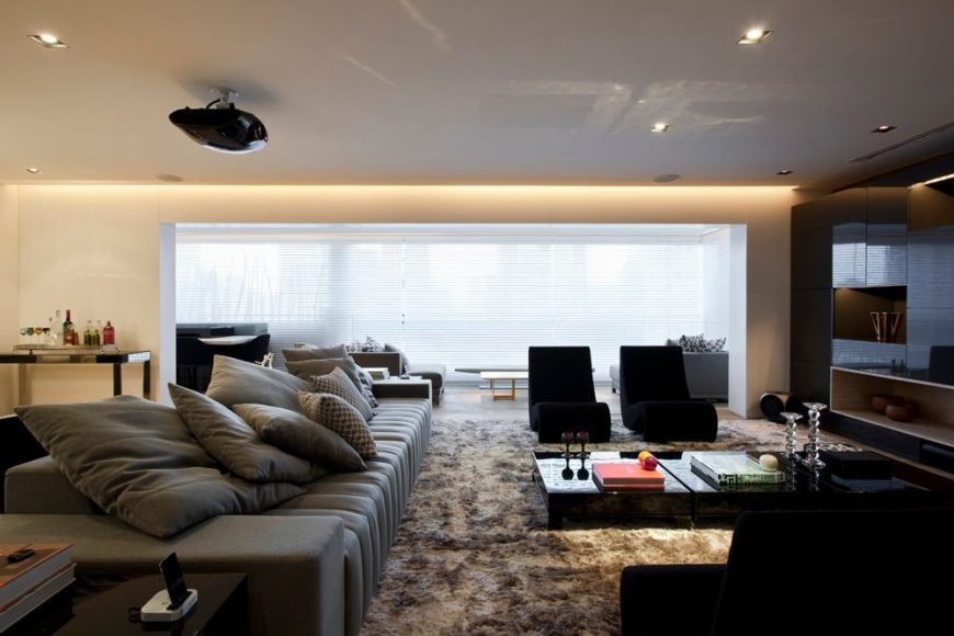 A shot of the formal living room showing the low profile sofa that is piled high with soft pillows. Modern recliners sit to the right in black. A plush area rug adds another dimension of texture to the space.