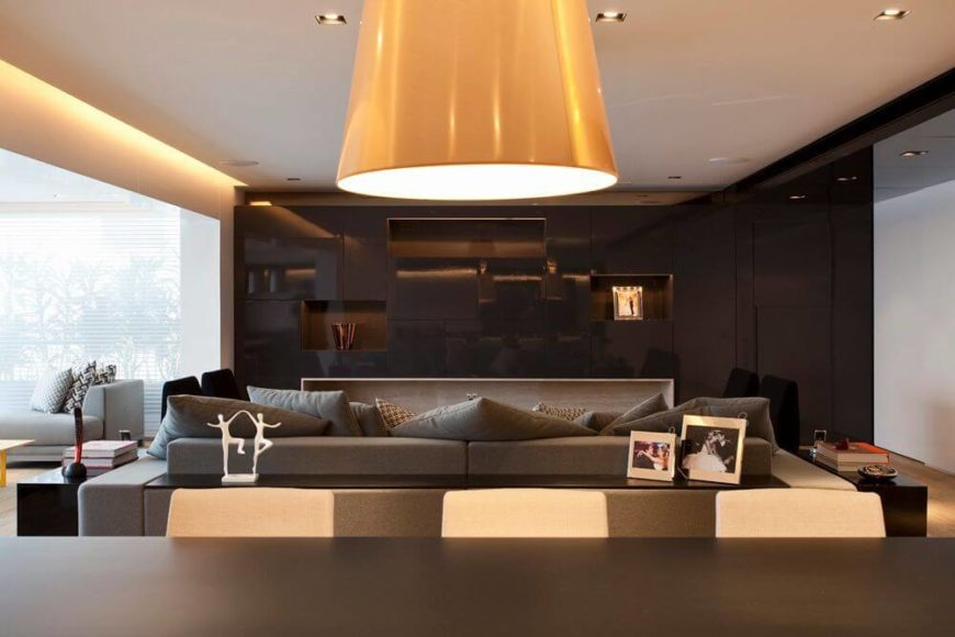 A view across the dining table at the modern entertainment center of the living room. Small cubbies are dispersed throughout the glossy brown section and backlit to best display the family's accents.