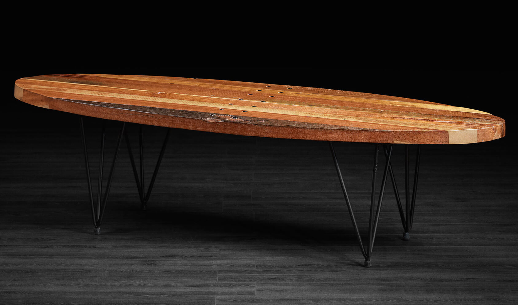 This coffee table is a striking, contemporary design incorporating a more surfboard-like surface over triangular wireframe legs. The mixture of rich natural wood and thin black metal makes for a bracing combination.