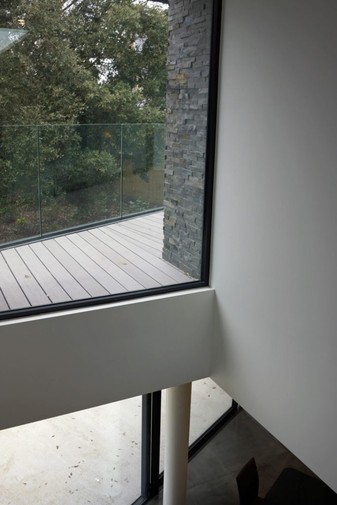 Over the central stair void, we can see down into the dining room and through full height glazing toward the second floor balcony.