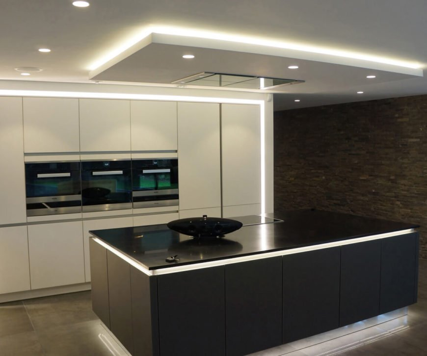 """Moving inside, we first visit the kitchen, centering on an immense black island that """"floats"""" over the floor, courtesy of intricately placed lighting. Built-in strips of light on the lower and upper edges create a unique counterpoint to the sleek white cabinetry of the room."""