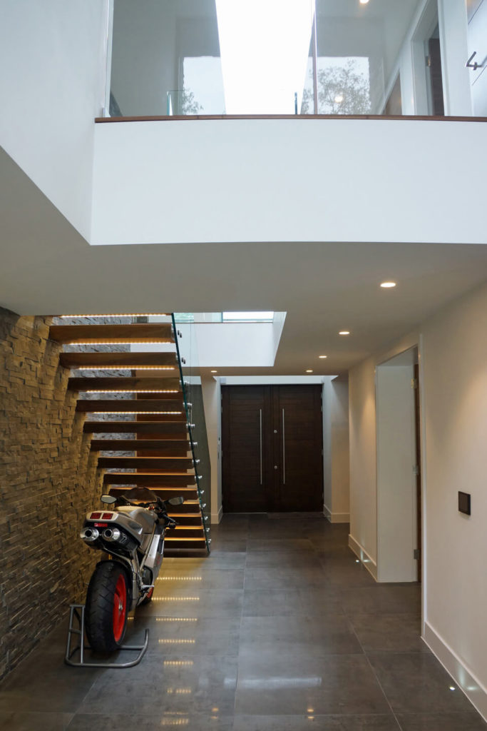 Tucked beneath the unique staircase is the owner's motorcycle, creating a discreet display space for the bike. The main hall here leads from the front entrance into the main open-plan space.