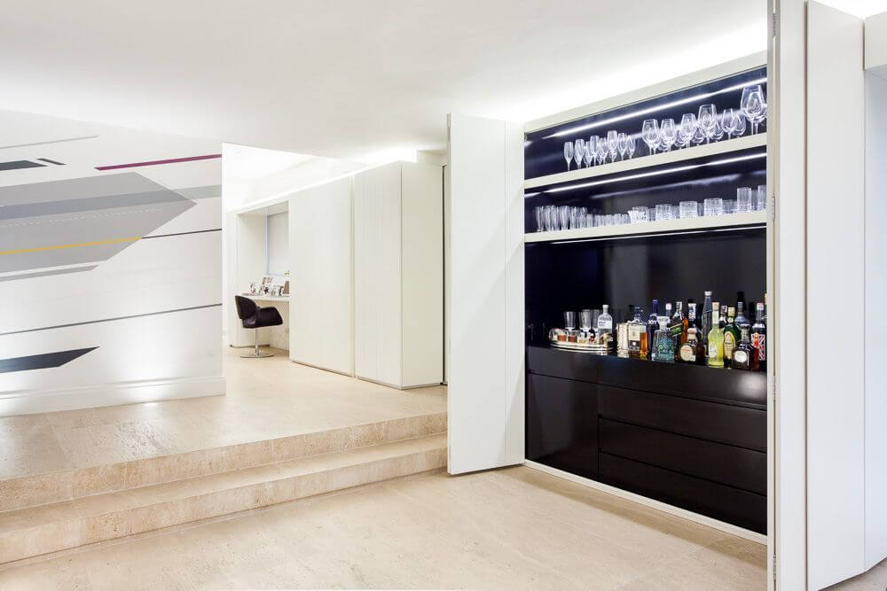 The open, breezy hallway between the open-concept living areas and the family room has an enormous black home bar that can be neatly tucked away behind pocket doors for an almost seamless appearance.