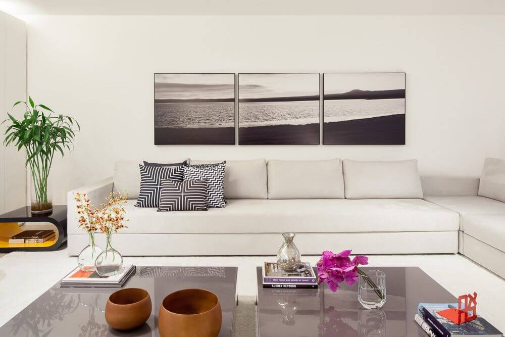 A close up on the dual coffee tables in the center of the seating arrangement and the high-gloss surface that reflects light. Three canvas prints above the sofa capture the serenity of a beach.