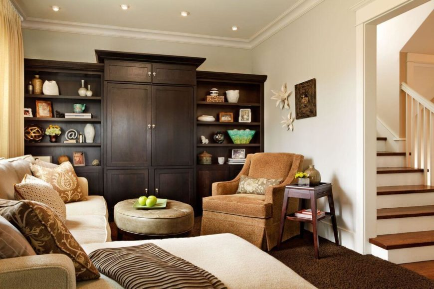 The lower level family room has gorgeous dark wood built-ins on the far wall, including a massive entertainment center with bookshelves on either side. The cream sectional has a wide chaise perfect for curling up on.