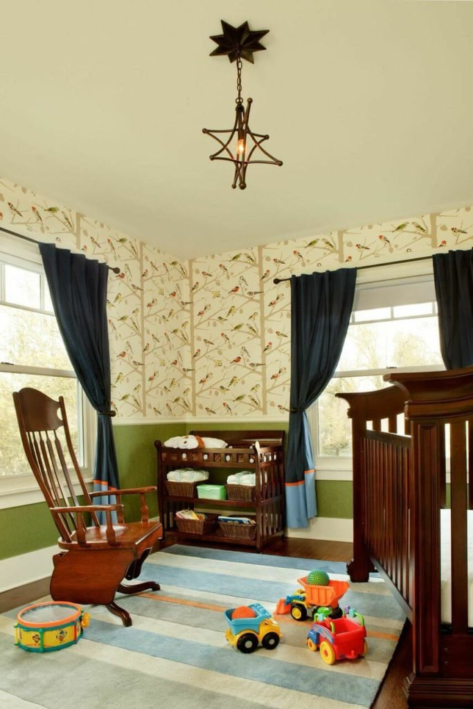 A view of the entire nursery. The modestly sized room's crib sits at a diagonal to the rocking chair. The upper half of the walls above the chair rail has a sweet wild bird wallpaper.
