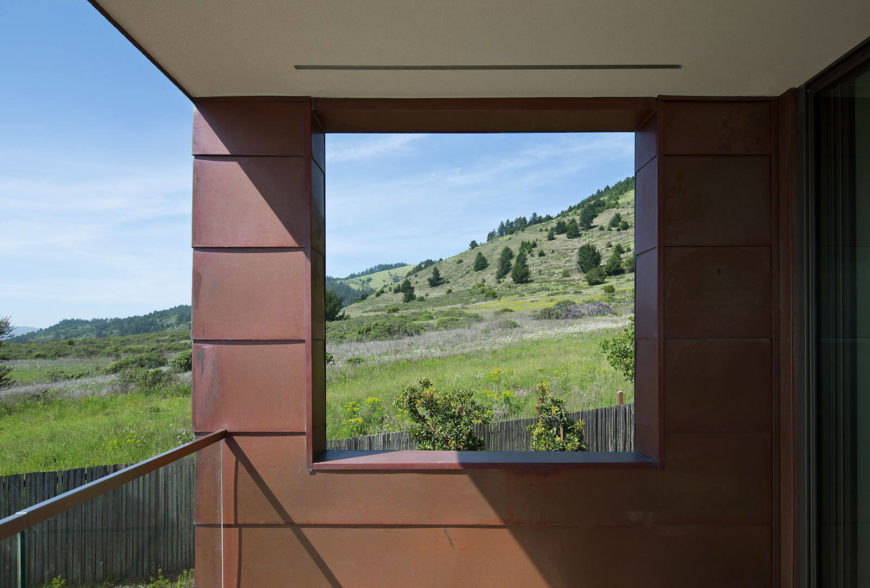 Viewed from the upper floor balcony, we see the lush rolling hillside leading toward the ocean. The worn look of copper and zinc helps connect the home to the environment.