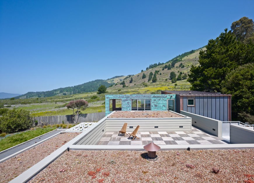 With built-in rooftop stair access, the home features a discreet patio up here, defined by checkerboard wood panel flooring and surrounded by rock gardens.