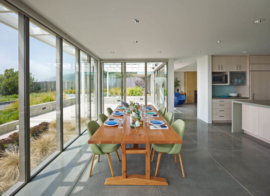 The main floor features an open-plan design, with the kitchen and dining space standing in sunlight through an expansive set of full height windows. Large format tile flooring contrasts with white walls and rich natural wood table.