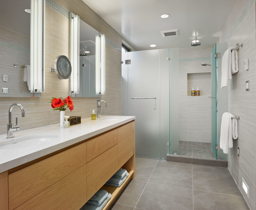 The bathroom features a firmly ultra-modern look, with smoked glass shower enclosure, large format tile flooring, and a rich wood dual vanity topped with white marble.