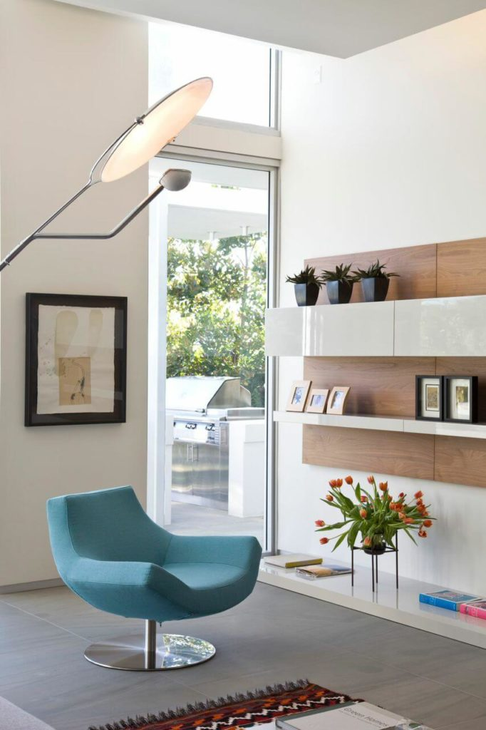 A close up on one of the cozy and modern armchairs next to the floating shelves on the back wall.